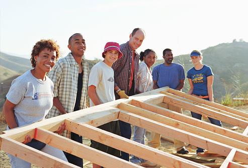 Nhóm người nâng tường nhà chưa hoàn thành