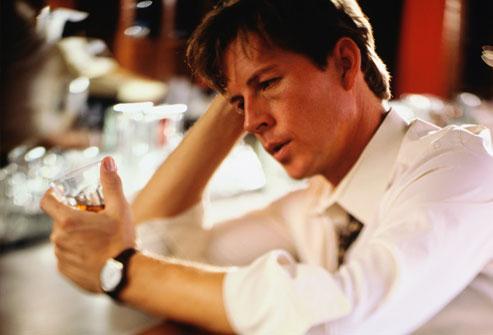 Người đàn ông ngồi tại quầy bar nhìn vào ly rượu