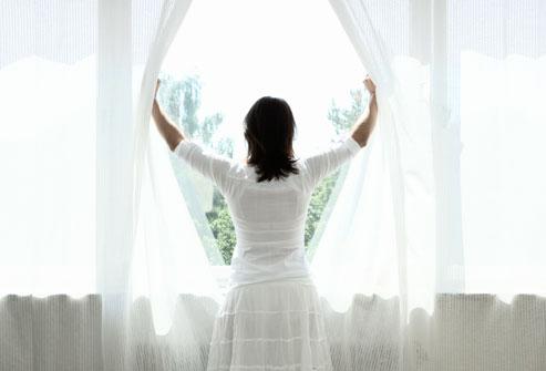 Người phụ nữ mở rèm cửa, nhìn ra ngoài cửa sổ