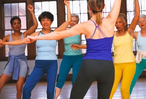 Nhóm phụ nữ có người hướng dẫn trong lớp tập thể dục