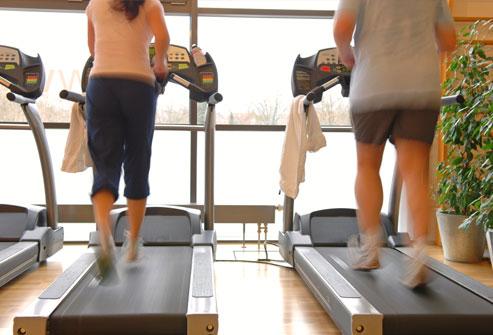 cặp đôi trên máy chạy bộ trong phòng tập thể dục