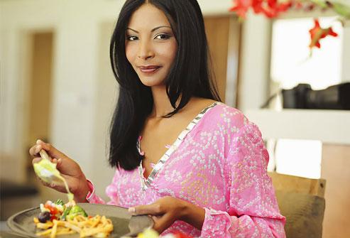 Người phụ nữ trẻ ở bàn với đĩa thức ăn, mỉm cười